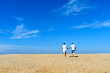 Romantic couple wakling on the beach