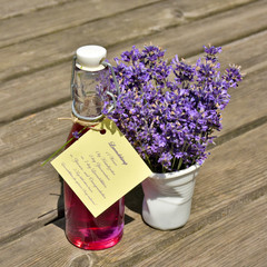 Homemade lavender syrup in a glass bottle with a bouquet of lavender blossoms