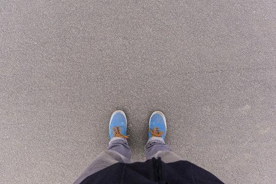 Asphalt ground, feet and shoes on floor