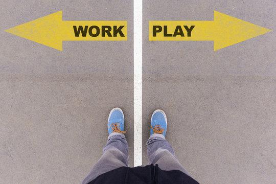 Work vs Play text arrows on asphalt ground, feet and shoes on fl
