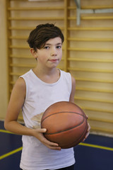 teenager boy basketball player in gym with ball