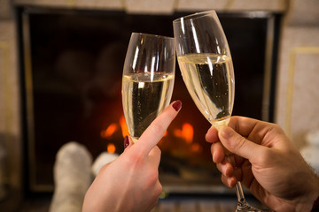 Closeup of couple's hands with glass of champagne near fireplace