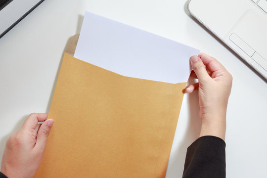 Businesswoman hands holding the blank paper in envelope - business