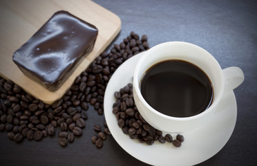 Hot coffee in a white cup and chocolate cake shot on a dark background.