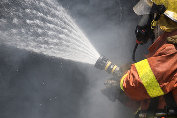 firefighter water spray by high pressure fire hose