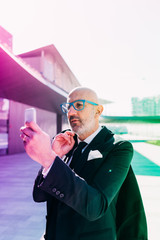 Middle-age contemporary businessman outdoor in the city using smart phone taking picture - sharing, technology, social network concept