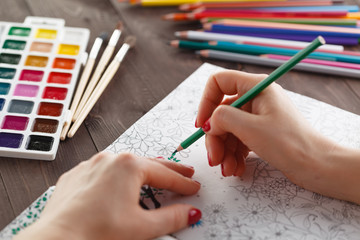 adult woman relieving stress by painting coloring book for relax