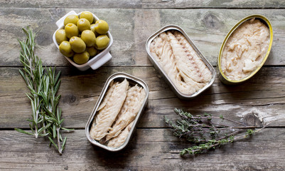 Canned fish and olives on rustic wooden boards