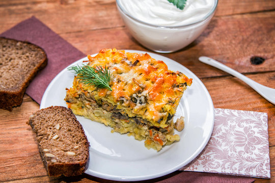 Homemade Shepherd's Pie served with sour cream and bread with sunflower seeds on wooden background
