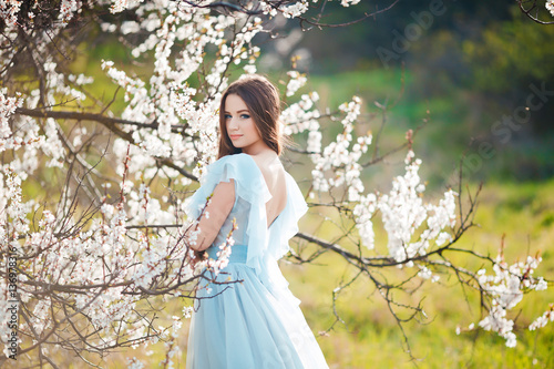Spring touch. Happy beautiful young woman in blue dress enjoy fresh flowers  and sun light in blossom park at sunset. 77dde2a0c