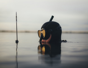 Spear fisherman submerged in water with speargun