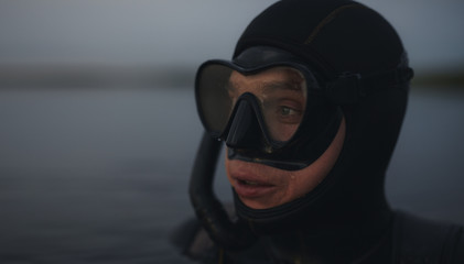 Scuba diver submerged in water looking away