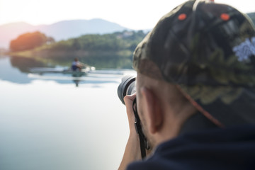 Photographer in nature taking pictures to a beautiful lake