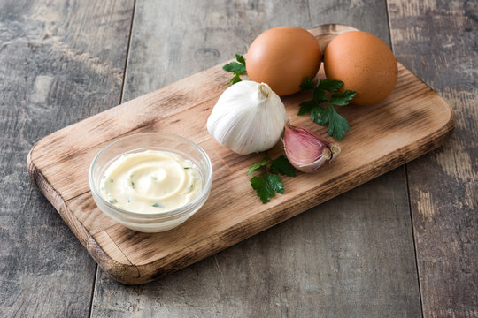 Aioli sauce and ingredients on wooden background