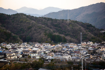 Wide angle view of the suburban houses of Nobeoka, Kyushu, Japan, surrounded by mountains covered in trees. Early spring. Travel and tourism concept.
