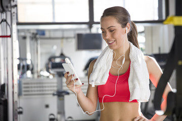 Cheerful beautiful young woman  listening to music in the gym