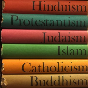 Colorful stack of religious books in Hinduism, Protestantism, Judiasm, Islam, Catholicism, Buddhism