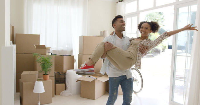 Ecstatic young couple celebrating their new home with the young man holding his wife in his arms as she grins and laughs at the camera