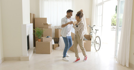 Happy young couple celebrating moving home dancing together in the living room surrounded by packing boxes