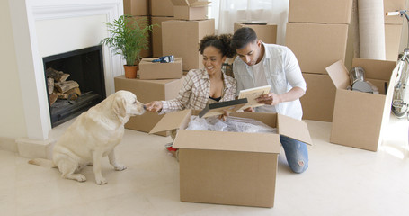 Young woman petting her pet dog as it sits calmly watching her and her husband pack their belongings ready to move house