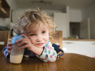 Girl with milk bottle looking away while sitting at table