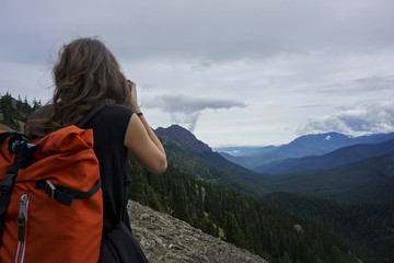 Rear view of female hiker standing on top of mountain against cloudy sky