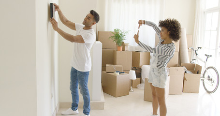 Young couple hanging pictures in their new home aligning it on the wall together working as a team