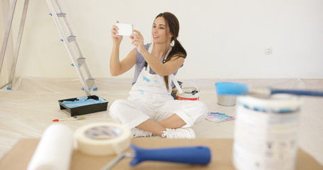 Young woman renovating her home taking a selfie of herself sitting on the floor surrounded by paint  tools and a stepladder