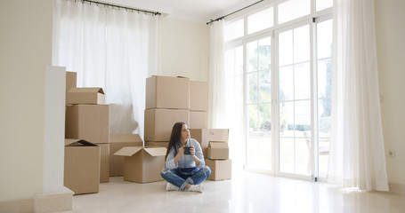 Young woman starting a new life in a new home sitting drinking coffee on the floor of the living room surrounded by brown cardboard boxes