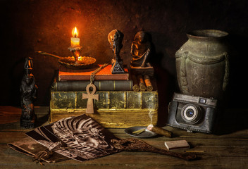 Classic still life with vintage books placed with old jar, illuminated candle, camera,old pictures,cigar and some ancient Egyptian sculptures on rustic wooden background.