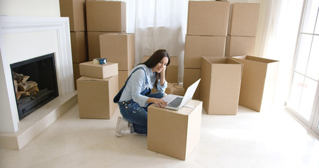 Young woman using a laptop on a cardboard box as she catches up with her social media after moving into a new home