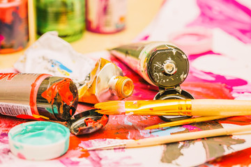 Painter workplace with tubes of multicolor oil paint and paintbrushes on painted paper close up