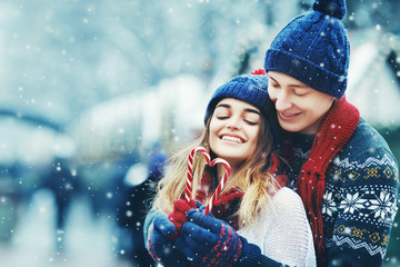 Outdoor portrait. Young beautiful happy smiling couple posing on street.  Models hugging, looking at candy canes, wearing stylish winter clothes. Snowfall. City lifestyle. Copy, empty space for text