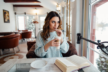 Woman drinking hot coffee latte in cafe