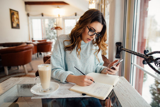 Young business woman in cafe writes notes in notebook from smartphone