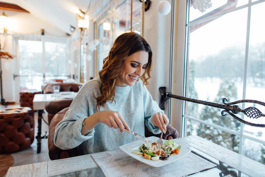 Smiling woman eating fresh salad in restaurant