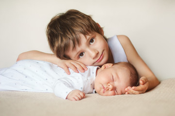 older brother hugging newborn baby