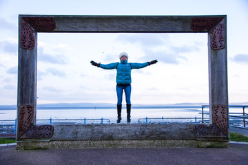 Model in big picture frame at Morecambe seafront jumping and having fun