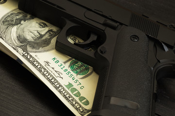 trigger gun on banknotes. concept of illegal arms trafficking and criminal offenses