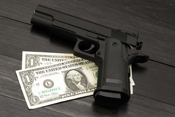Black gun on banknotes. Concept of armed criminal offenses