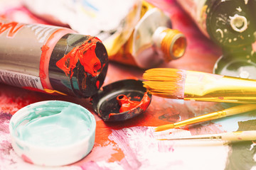 Painter workplace with tubes of multicolor oil paint and paintbrushes on painted paper close up with selective focus