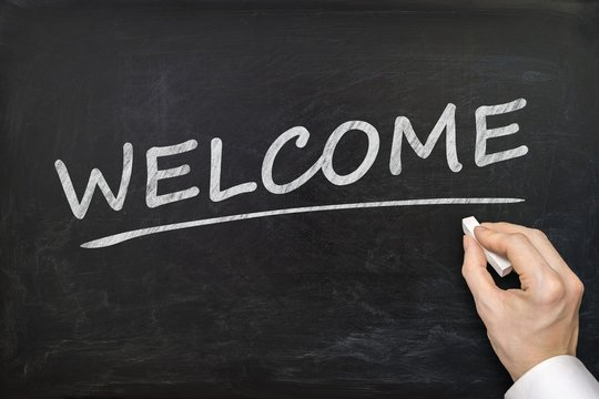Hand is writing Welcome word on blackboard. Invitation concept.