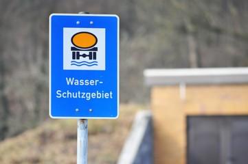 Zeichen Wasserschutzgebiet mit Quellfassung der öffentlichen Wasserversorgung im HintergrundZeichen Wasserschutzgebiet mit Quellfassung der öffentlichen Wasserversorgung im Hintergrund