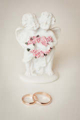 Wedding rings and Cupid statuette, wedding accessories