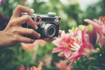 Close up woman's hand with vintage camera focus shooting flowers