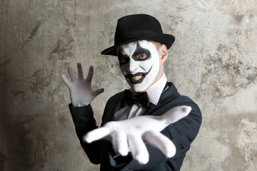 Scary evil clown wearing a bowler hat on wall
