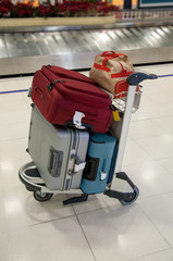 Airport luggage cart and luggage of tourists.