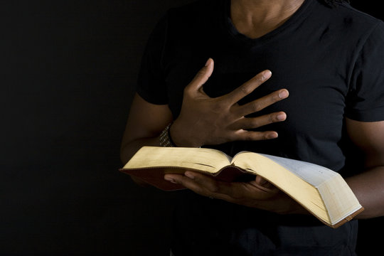 Man reading a bible isolated on black.