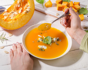 Woman hands holding spoon and a bowl of healthy pumpkin  soup.