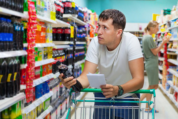 Young caucasian guy in supermarket is looking into shelves with goods and holding list of necessary purchases. Shopping in grocery store